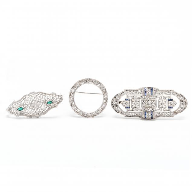 three-white-gold-gem-set-brooches