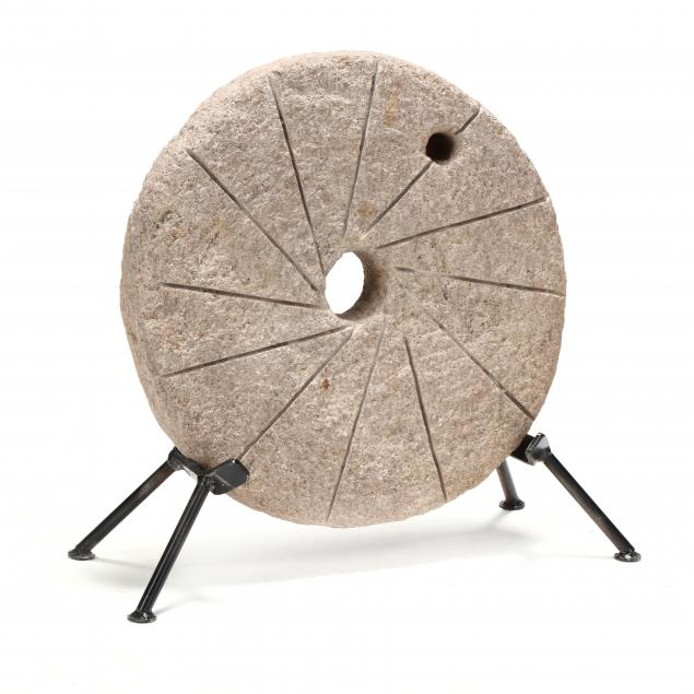 a-small-antique-millstone-on-stand
