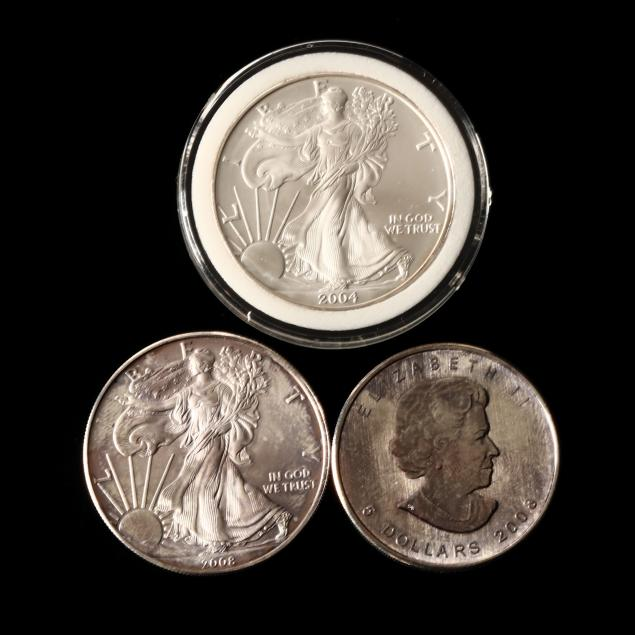 two-american-silver-eagles-and-a-canadian-maple-leaf